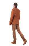 Back view of walking  businessman in jeans and jacket Royalty Free Stock Image