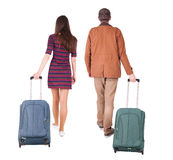 Back view of walking  couple  with suitcase. Royalty Free Stock Image
