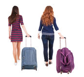 Back view of walking  couple  with suitcase. Stock Image