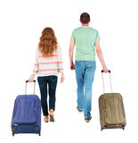 Back view of walking  couple  with suitcase. Royalty Free Stock Photos