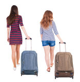 Back view of walking  couple  with suitcase. Stock Images