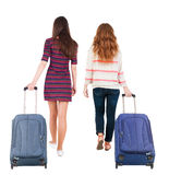 Back view of walking  couple  with suitcase. Royalty Free Stock Photo