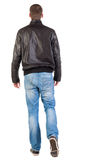 Back view of walking handsome man in jacket. Stock Photography