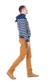 Back view of walking handsome man in jeans and striped sweater. Royalty Free Stock Photos