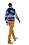 Back view of walking handsome man in jeans and striped sweater. Stock Photo