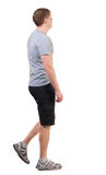 Back view of walking handsome man in shorts and sneakers. Stock Photo