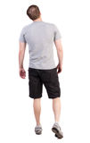 Back view of walking man in shorts and sneakers Stock Image