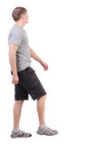 Back view of walking handsome man in shorts and sneakers Royalty Free Stock Images