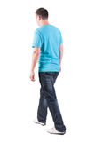 Back view of walking handsome man in t-shirt. Royalty Free Stock Images