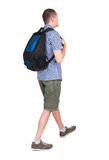 Back view of walking man with backpack. Stock Photo