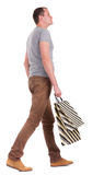Back view of walking   man in gray shirt with shopping bags. Royalty Free Stock Photo
