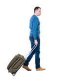 Back view of walking  man  with suitcase. Royalty Free Stock Photography