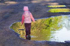 Back view of walking in spring puddle preschooler girl wearing purple nylon and pink bucket hat Stock Photo