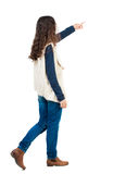 Back view of walking  woman. beautiful redhead girl pointing. Stock Photo