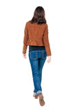 Back view of walking woman in brown jacket. Beautiful brunette girl in motion. backside view of person. Rear view people collection. Isolated over white royalty free stock images