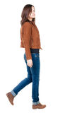 Back view of walking  woman in brown jacket. Royalty Free Stock Image