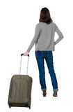 Back view of walking  woman  in cardigan with suitcase. Pretty girl waits for airplane or train. beautiful  girl in motion.  backside view of person.  Rear Royalty Free Stock Photography