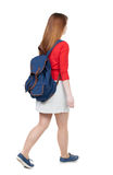 Back view of walking  woman in dress with backpack. Royalty Free Stock Photography