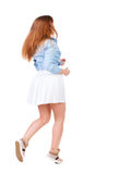 Back view of walking  woman in dress. beautiful redhead girl in Stock Photography