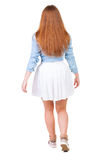 Back view of walking  woman in dress. beautiful redhead girl in Stock Photo