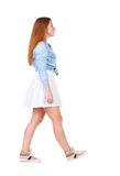 Back view of walking  woman in dress. beautiful redhead girl in Royalty Free Stock Image
