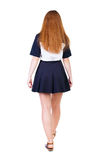 Back view of walking  woman in dress. beautiful redhead girl in Royalty Free Stock Photography
