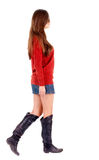 Back view of  walking woman  in  in dress and sweater. Beautiful brunette girl in motion. sad woman in a miniskirt and boots.  backside view of going person Royalty Free Stock Photos