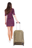 Back view of walking  woman  with green suitcase. Beautiful brunette girl in motion.  backside view of person.  Rear view people collection. Isolated over Royalty Free Stock Photo