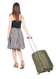 Back view of walking woman  with green suitcase. Royalty Free Stock Images