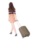 Back view of walking  woman  with green suitcase. Back view of walking woman  with green suitcase. Beautiful brunette girl in motion. Girl on the heels rolls Stock Photography