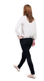 Back view of walking  woman in jeans. beautiful blonde girl in m Royalty Free Stock Photography