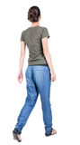Back view of walking woman in jeans. Beautiful brunette girl in motion. backside view of person. Rear view people collection. Isolated over white background stock images