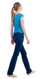 Back view of walking  woman  in   jeans and shirt. Beautiful blonde girl in motion. happy cute girl looks at something with interest at the top. backside view Royalty Free Stock Photos