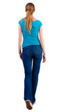 Back view of walking  woman  in   jeans and shirt. Beautiful blonde girl with pony tail in motion.  backside view of person.  Rear view people collection Royalty Free Stock Photos