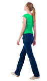 Back view of walking  woman  in   jeans and shirt. Stock Photos