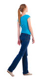 Back view of walking  woman  in   jeans and shirt. Back view of walking  woman  in   jeans and T-shirt. beautiful blonde girl in motion. relaxed gait pretty Royalty Free Stock Image