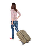 Back view of walking  woman  with suitcase. Royalty Free Stock Photo