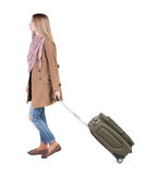 Back view of walking  woman  with suitcase. beautiful girl in mo Royalty Free Stock Photography