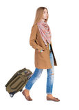 Back view of walking  woman  with suitcase. beautiful girl in mo Stock Photo