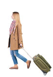 Back view of walking  woman  with suitcase. beautiful girl in mo Stock Image