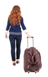 Back view of walking  woman  with suitcase. Royalty Free Stock Photography