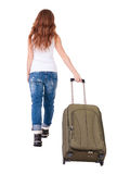 Back view of walking  woman  with suitcase. Royalty Free Stock Images