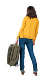 Back view of walking  woman  with suitcase. Stock Photos