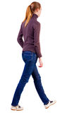 Back view of walking  woman  in  sweater. Sad blonde in white shoes out into the distance beautiful blonde girl in motion.  backside view of person.  Rear Stock Images