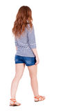 Back view of walking young beautiful  redhead woman. Stock Image