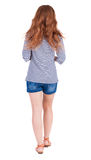 Back view of walking young beautiful  redhead woman. Royalty Free Stock Images