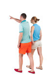 Back view of walking young couple (man and woman) pointing. Going tourists in shorts considering attractions. Rear view people collection. backside view of Stock Photos