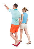 Back view of walking young couple (man and woman) pointing. Royalty Free Stock Photography