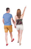 Back view of walking young couple (man and woman) pointing. Royalty Free Stock Photos