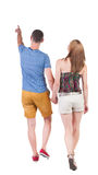 Back view of walking young couple (man and woman) pointing. Stock Images